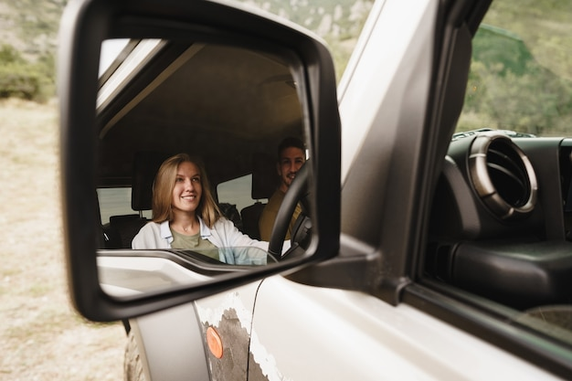 Beautiful young couple sitting on front passenger seats and driving a car