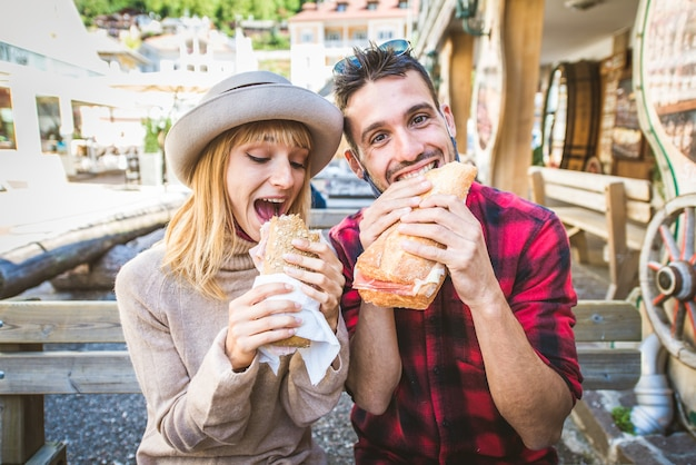 バーのレストランに座ってサンドイッチを食べる美しい若いカップル