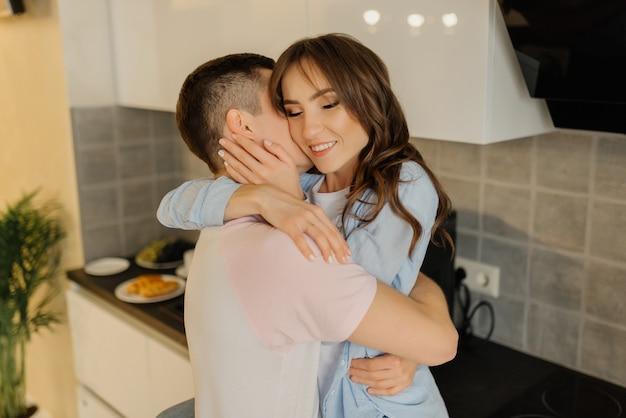 自宅のキッチンで一緒に時間を過ごす美しい若いカップル。愛の少女と彼女のボーイフレンドは抱いています。愛するカップルのコンセプトです。