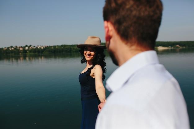 美しい若いカップルは湖の木製の桟橋に時間を費やしています