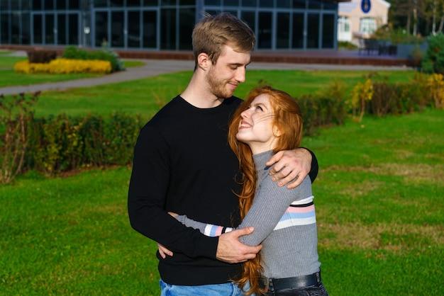美しい若いカップルは、近代的な建物と緑の芝生を背景に都市公園の抱擁に立っています
