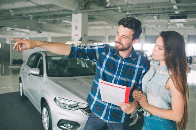 구매할 차를 선택하는 대리점에 서있는 아름다운 젊은 부부