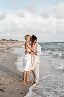 . beautiful young couple standing face to face and kissing while on beach vacation