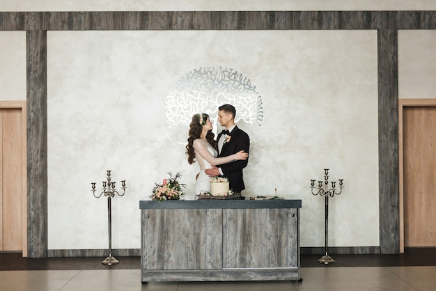 Beautiful young couple standing and holding a wedding cake with luxurious interior