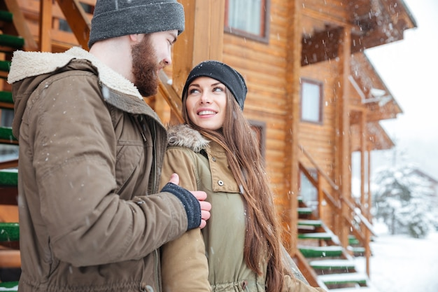 Beautiful young couple standing and looking at each other near wooden cottage in winter