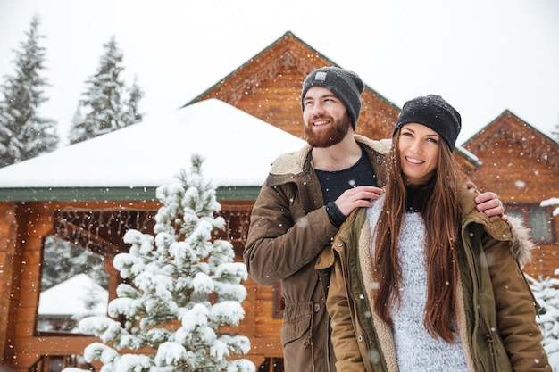 눈 덮인 날씨에 통나무 집 근처에 서있는 아름 다운 젊은 부부