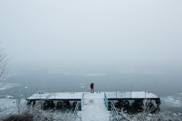 Beautiful young couple standing on a pier and looks at the frozen lake