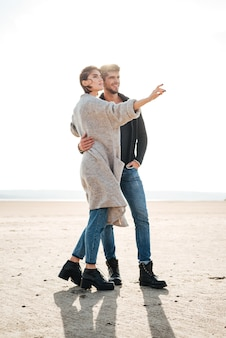 Beautiful young couple standing at the seashore in autumn