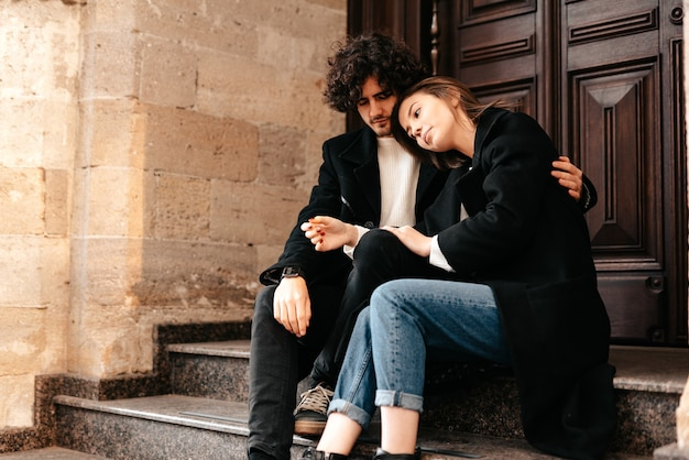 Beautiful young couple student couple in love sitting on the stairs in the city guy hugs a girl
