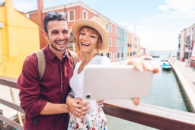 Beautiful young couple taking a selfie in venice, burano. happy woman and man in love travelling together.