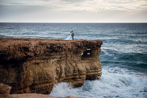 海沿いの岩の上で優しく抱きしめる美しい若いカップル