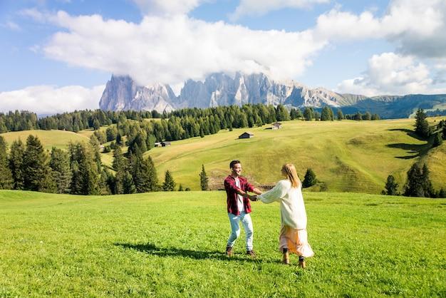 イタリアのドロミテを旅する美しい若いカップル。自然の中で日帰り旅行をしている2人の恋人