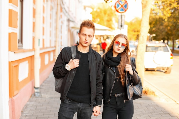 Beautiful young couple in trendy clothes with bags traveling together in the city