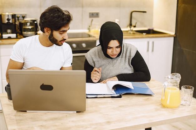 ノートパソコンを使用して、ノートに書いている、自宅のキッチンに座っている美しい若いカップル。黒のヒジャーブを着ているアラブの女の子。
