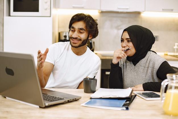ノートパソコンを使用して、ノートに書いている、自宅のキッチンに座っている美しい若いカップル。ヒジャーブを着ているアラブの女の子。