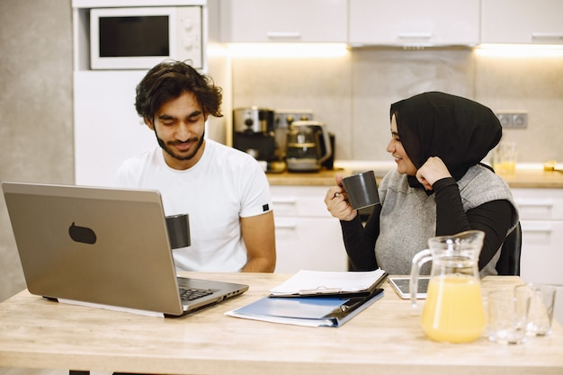 Beautiful young couple using a laptop, writing in a notebook, sitting in a kitchen at home. arab girl wearing black hidjab.