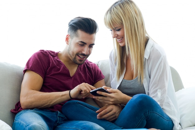 Beautiful young couple using mobile phone at home.