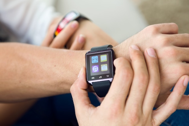 Beautiful young couple using a smartwatch at home.