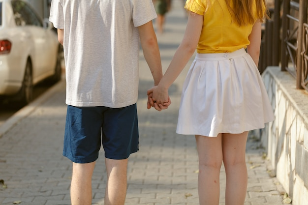 Beautiful young couple  walk hand in hand on the road