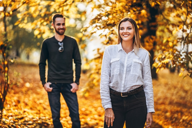 Beautiful young couple walking in the autumn park on a sunny day.