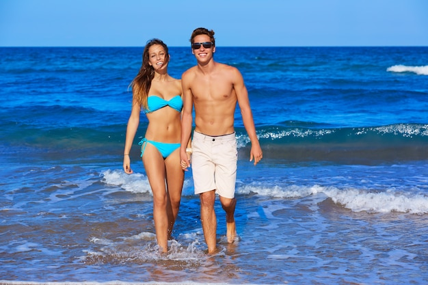 Beautiful young couple walking in the beach