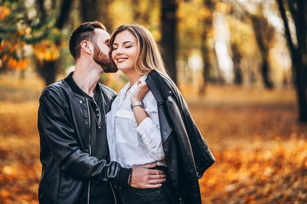 Красивая молодая пара гуляет в осеннем парке в солнечный день