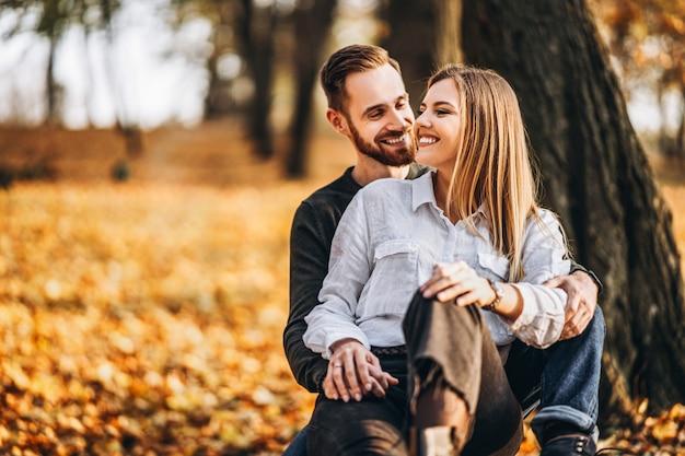 晴れた日に秋の公園で歩く美しい若いカップル