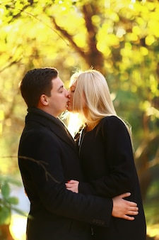 秋の公園で歩く美しい若いカップル