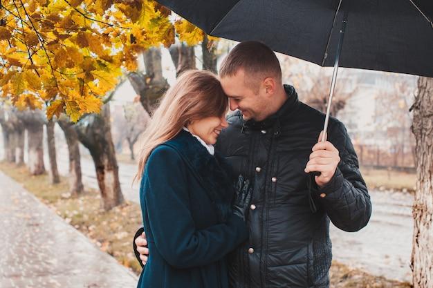 Красивая молодая пара гуляет под зонтиком в осенней аллее