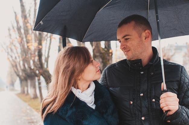 秋の路地で傘の下を歩く美しい若いカップル