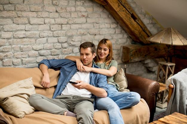Красивая молодая пара смотрит телевизор у себя дома