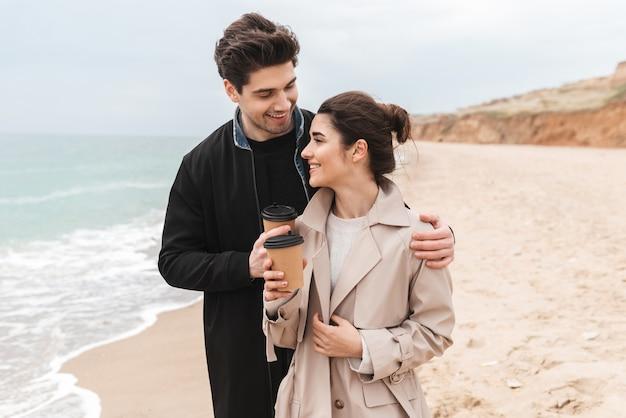 Красивая молодая пара в пальто гуляет на пляже, пьет кофе на вынос