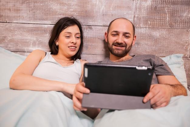 タブレットコンピューターを使用して夜ベッドに並んで座っているパジャマを着ている美しい若いカップル。
