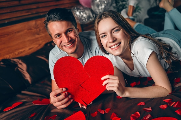 Beautiful young couple with a big red heart in their hands  in bedroom is lying on the bed and hugging. celebrating saint valentine's day.