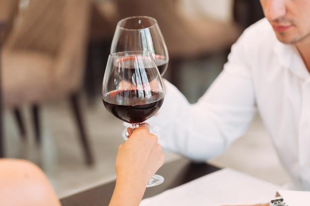 高級レストランで赤ワインのグラスと美しい若いカップル