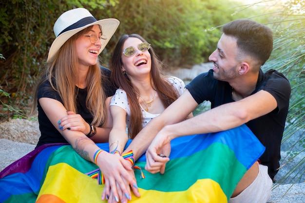 Lgbtコミュニティの平等な権利、虹色の旗を優しく抱き締めるレズビアンの少年と美しい若いカップル