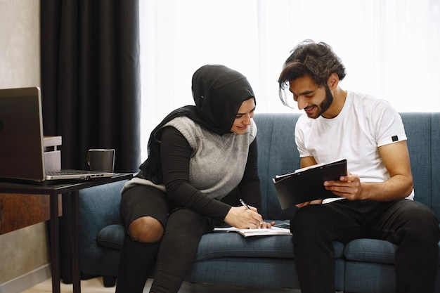 Beautiful young couple writing in a notebook, sitting on couck at home. arab girl wearing black hidjab.