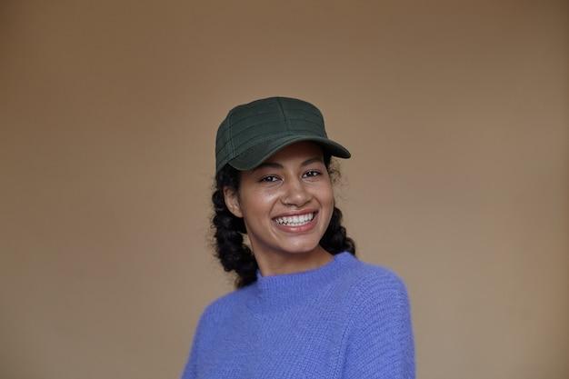 보라색 모직 스웨터와 녹색 야구 모자를 쓰고 캐주얼 헤어 스타일로 아름 다운 젊은 곱슬 갈색 머리 어두운 피부 여성, 고립 된 매력적인 미소로 찾고