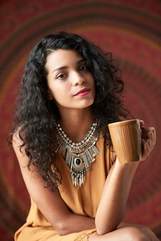 Beautiful young curly brunette posing and holding mug