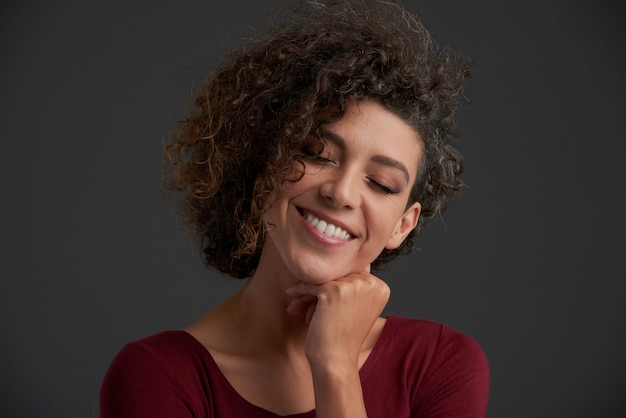 Beautiful young curly caucasian brunette posing in studio with closed eyes