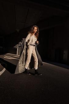 긴 코트를 입은 아름다운 곱슬머리 소녀, 니트 블라우스, 바지, 부츠를 신은 채 햇빛 아래 도시를 걷는다