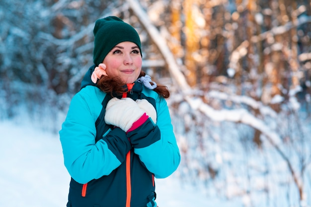 Beautiful young cute pretty woman is walking in a winter snowy forest or park in hat and gloves