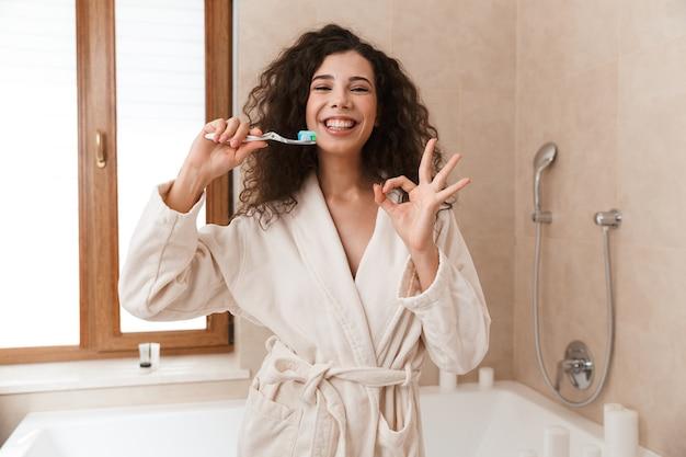 그녀의 이빨을 청소하는 욕실 칫 솔 질에 아름 다운 젊은 귀여운 여자.
