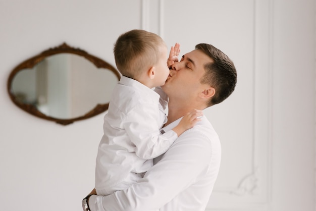 美しい若いお父さんと息子が寄り添って、家でスマートな服で遊ぶ