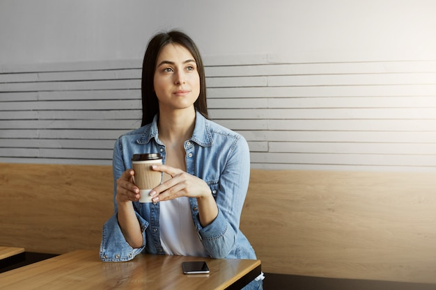 Beautiful young dark haired girl in denim shirt and white t-shirt drinks coffee, looking aside with relaxed expression and waiting friend that being late.