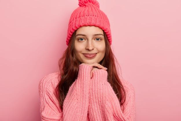 Bella giovane donna dai capelli scuri tiene le mani sul mento, indossa abiti invernali caldi, guarda volentieri la telecamera ha una bellezza naturale senza trucco.