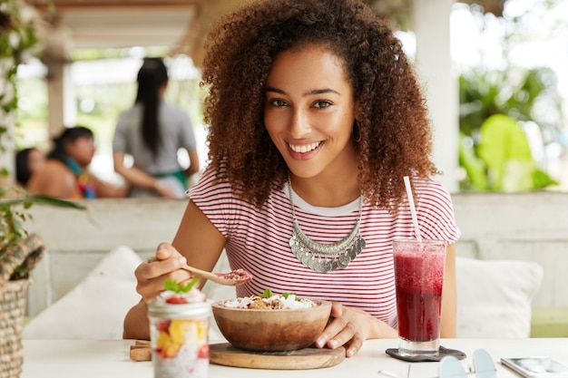 Beautiful young dark skinned female eats exotic dish and drinks cold summer cocktail, has pleased expression, sits in terrace cafe, has appealing appearance. people, eating, rest and lifestyle concept