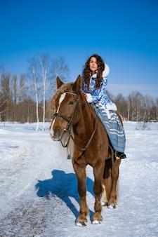 겨울에 말을 타고 전통 옷을 입고 아름 다운 젊은 검은 머리 여자