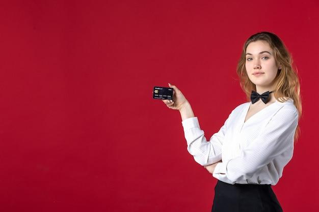 Красивая молодая решительная женщина-бабочка-сервер на шее и держит банковскую карту на красном фоне