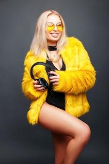 Красивая молодая девушка ди-джея с улыбкой позирует с наушниками в модных солнцезащитных очках и стильной желтой шубе на сером